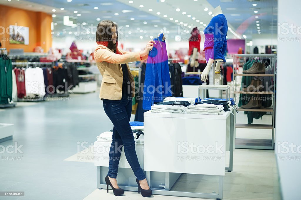 Attractive woman choosing cloths in shop stock photo