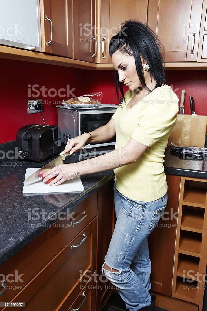 Attractive woman chopping apple in kitchen royalty-free stock photo