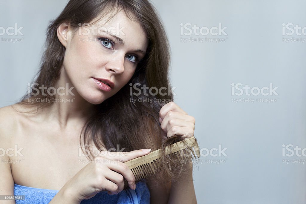 Attractive woman combing her hair stock photo