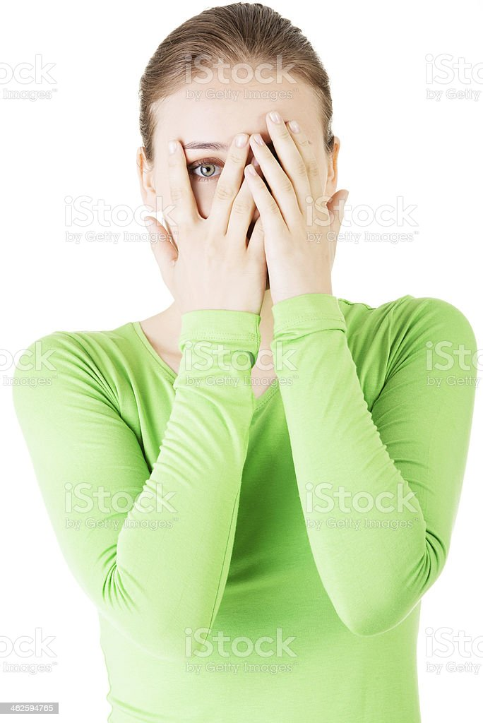 Attractive woman covering her face with both hands. stock photo