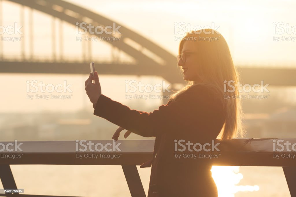 Attractive woman doing a selfie outdoors. stock photo