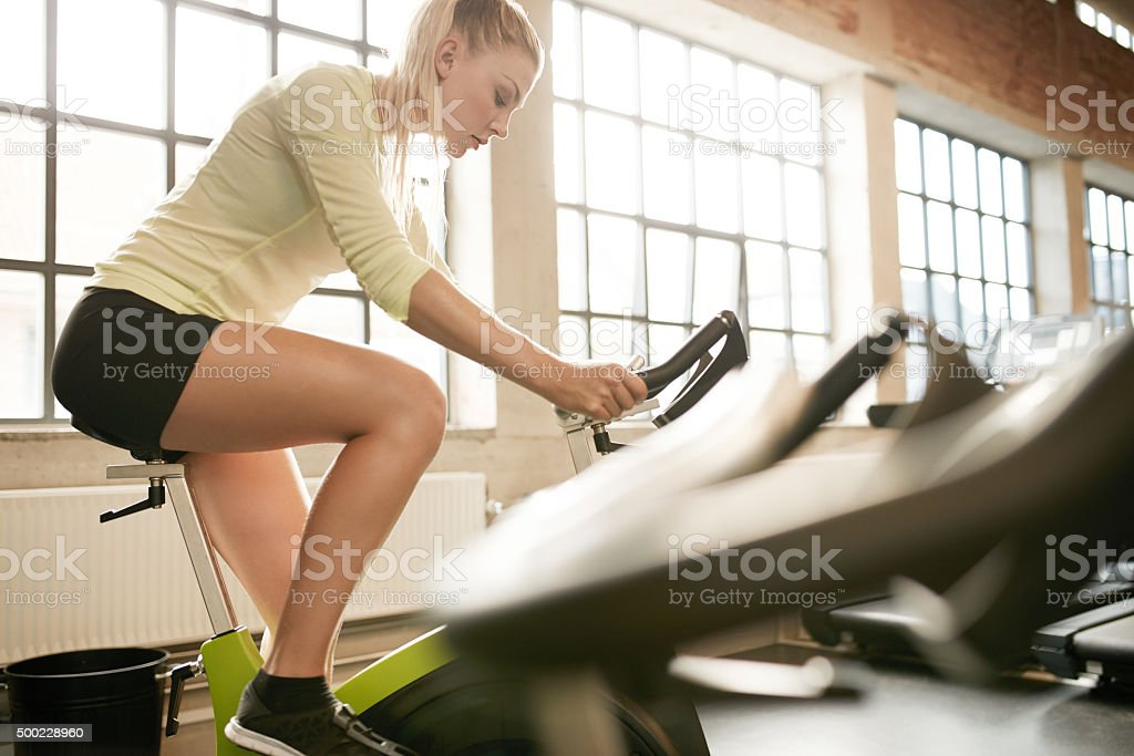 Attractive woman doing fitness on a stationary bike stock photo