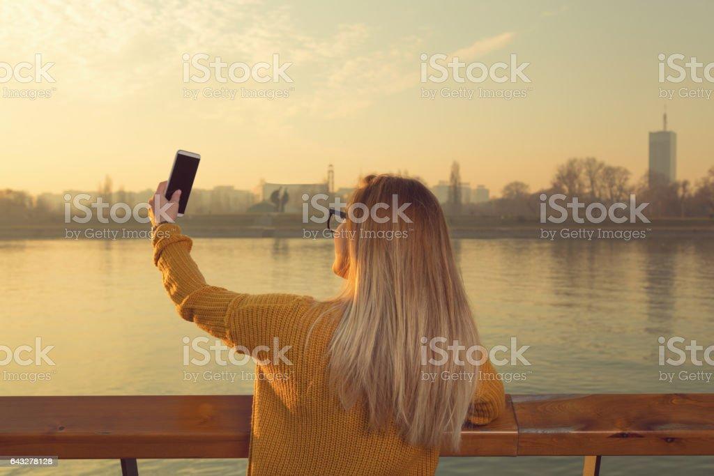 Attractive woman doing selfie outdoors. stock photo
