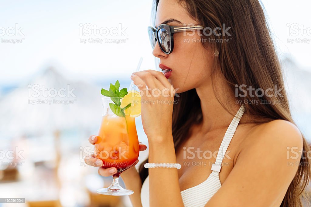 Attractive woman drinking cocktail side portrait stock photo