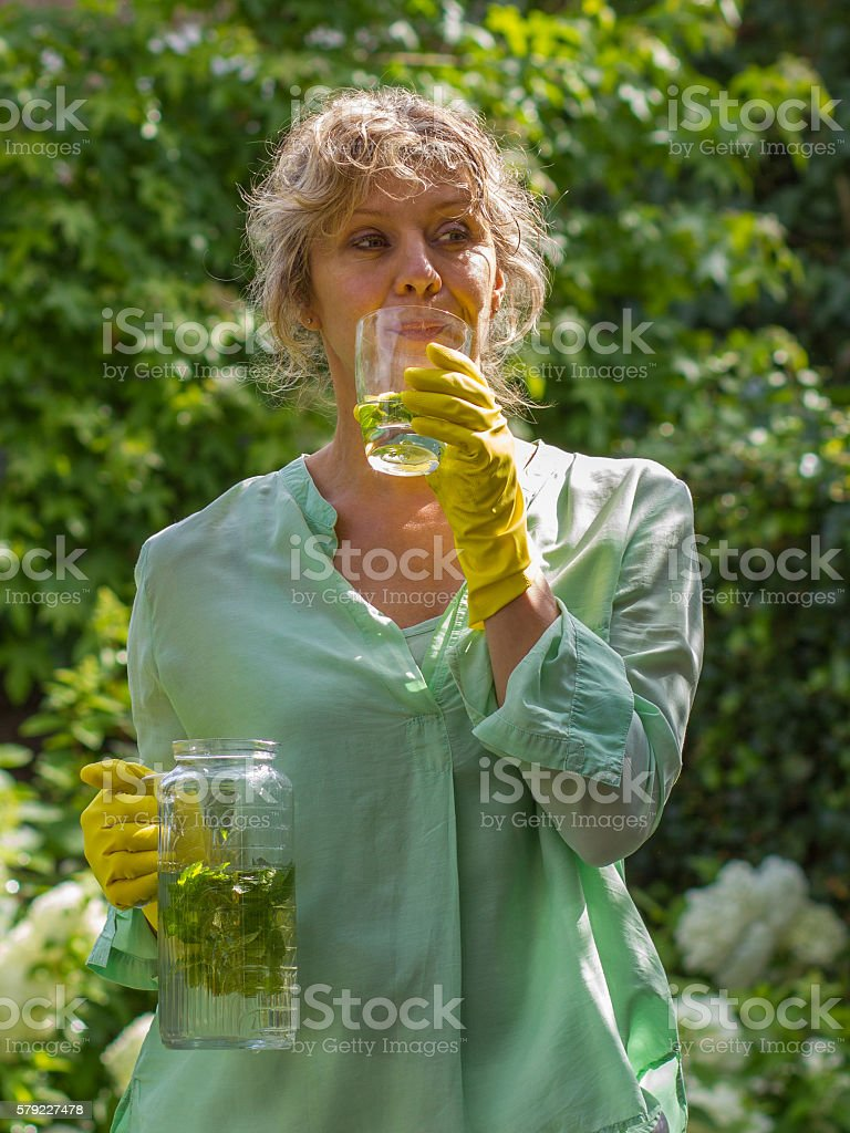 Attractive woman during pause drinking water with mint and lemon stock photo