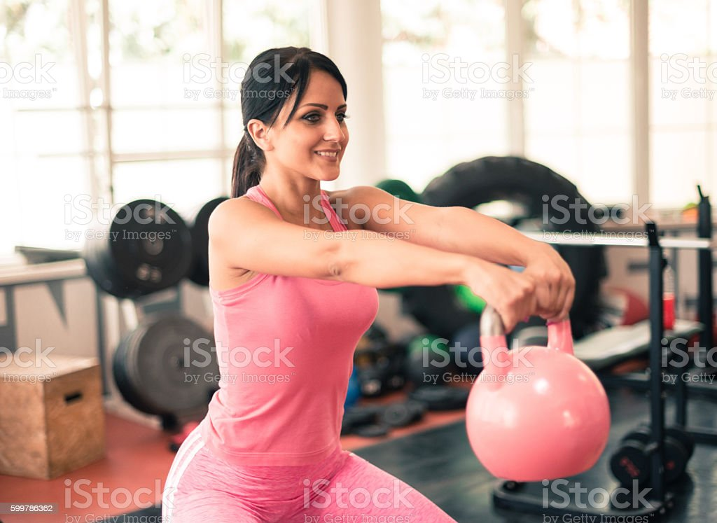 Attractive woman exercising with kettle bell stock photo