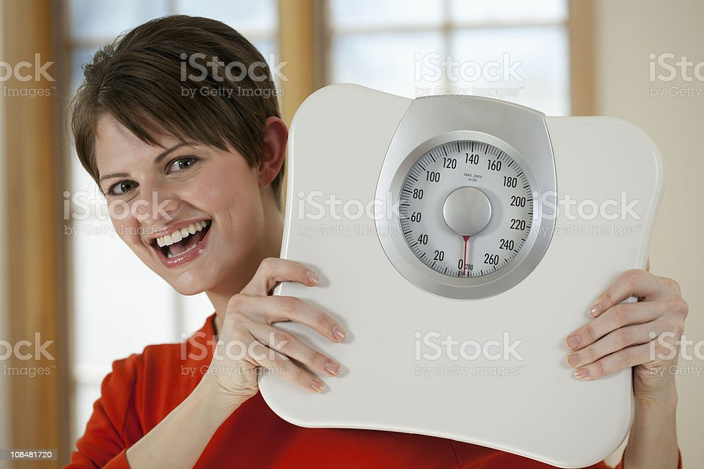 Attractive Woman Holding a Bathroom Scale royalty-free stock photo