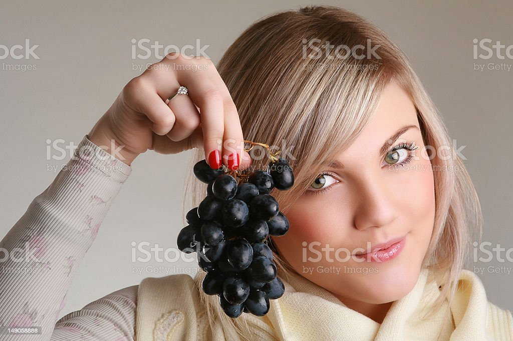 Attractive woman holding a bunch of grapes in studio royalty-free stock photo