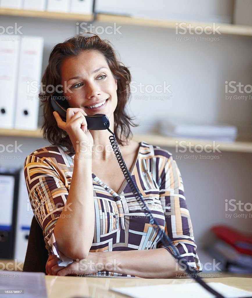 Attractive woman holding a telephone receiver at office desk royalty-free stock photo