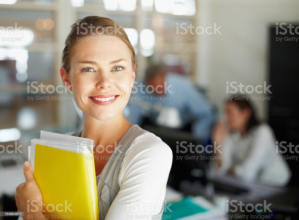 Attractive woman holding folder with colleagues in background royalty-free stock photo