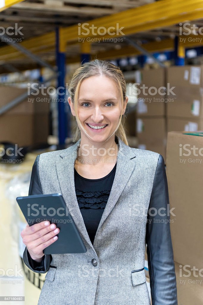 Attractive woman holding tablet in warehouse stock photo