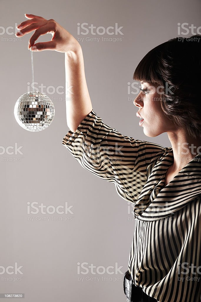Attractive Woman Holding Up a Small Disco Ball royalty-free stock photo