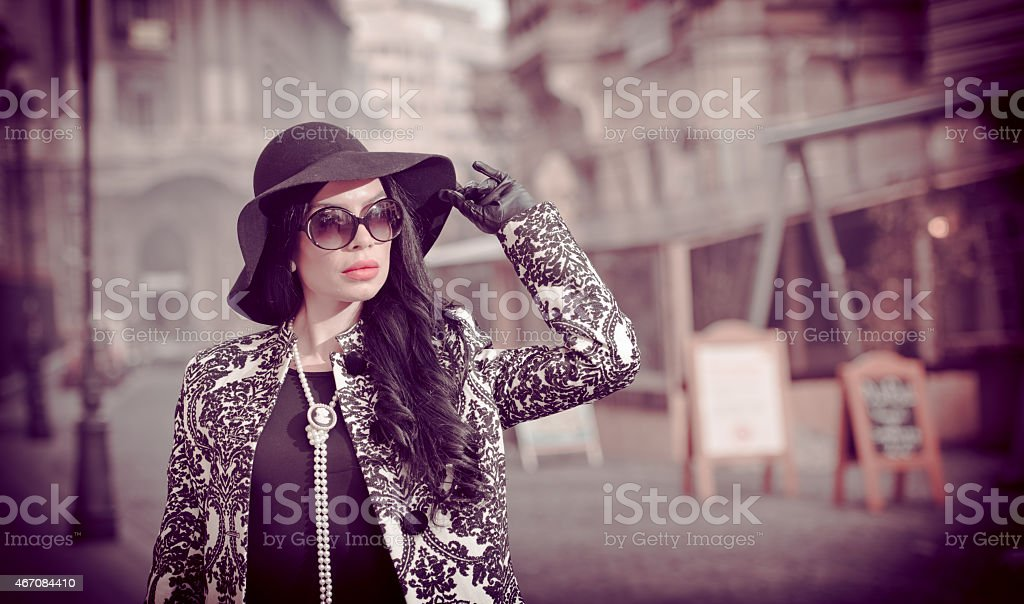 Attractive woman in a black hat and sunglasses stock photo
