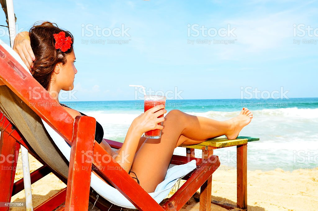 Attractive woman in bikini at beach drinking cocktail in summer stock photo