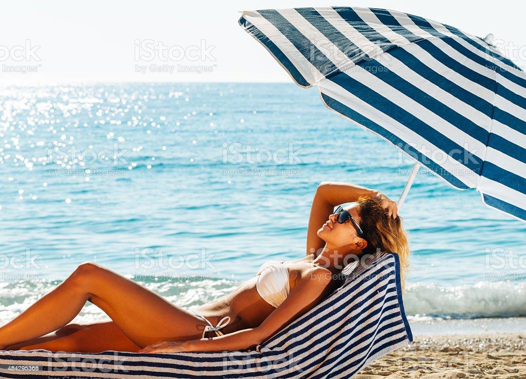 Attractive woman in bikini lying on beach in summer sunbathing stock photo