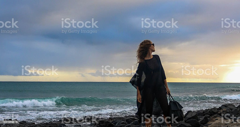 Attractive woman in black dress on the beach stock photo