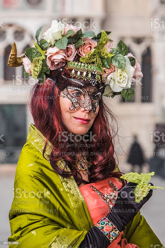Attractive woman in green costume poses at Venice Carnival stock photo