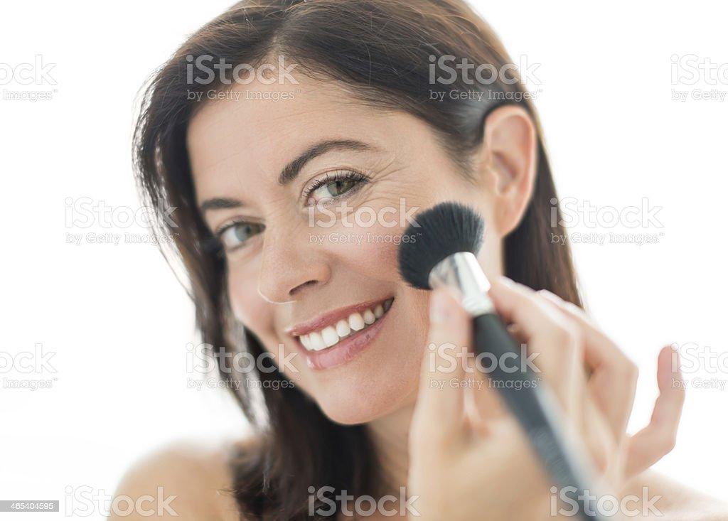 attractive woman in her forties applying makeup stock photo
