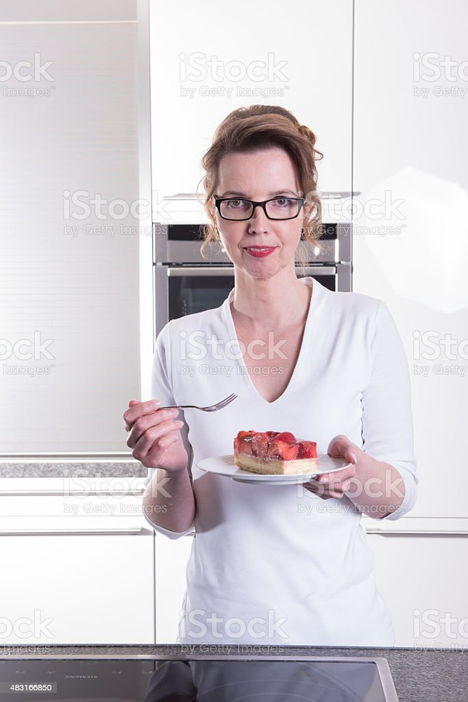 attractive woman in modern ktchen eating strawberry cake stock photo