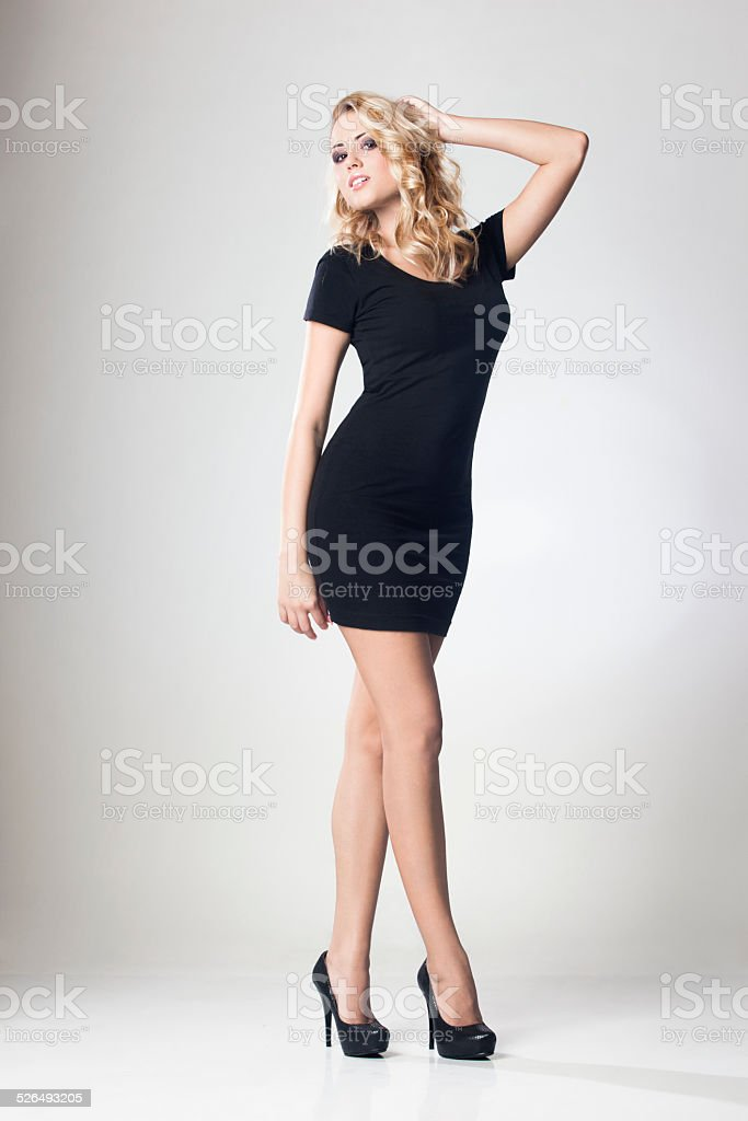 Attractive woman in short black dress stock photo