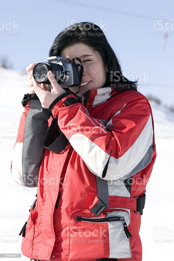 Attractive woman in sport wear holding a camera, winter outdoors royalty-free stock photo