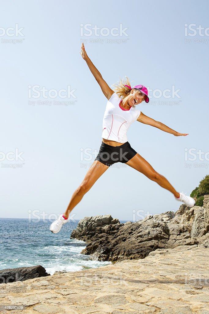 Belle femme en vêtements de sport sauter en plein air. photo libre de droits