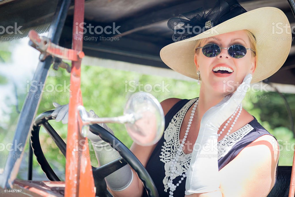 Attractive Woman in Twenties Outfit Driving an Antique Automobil stock photo