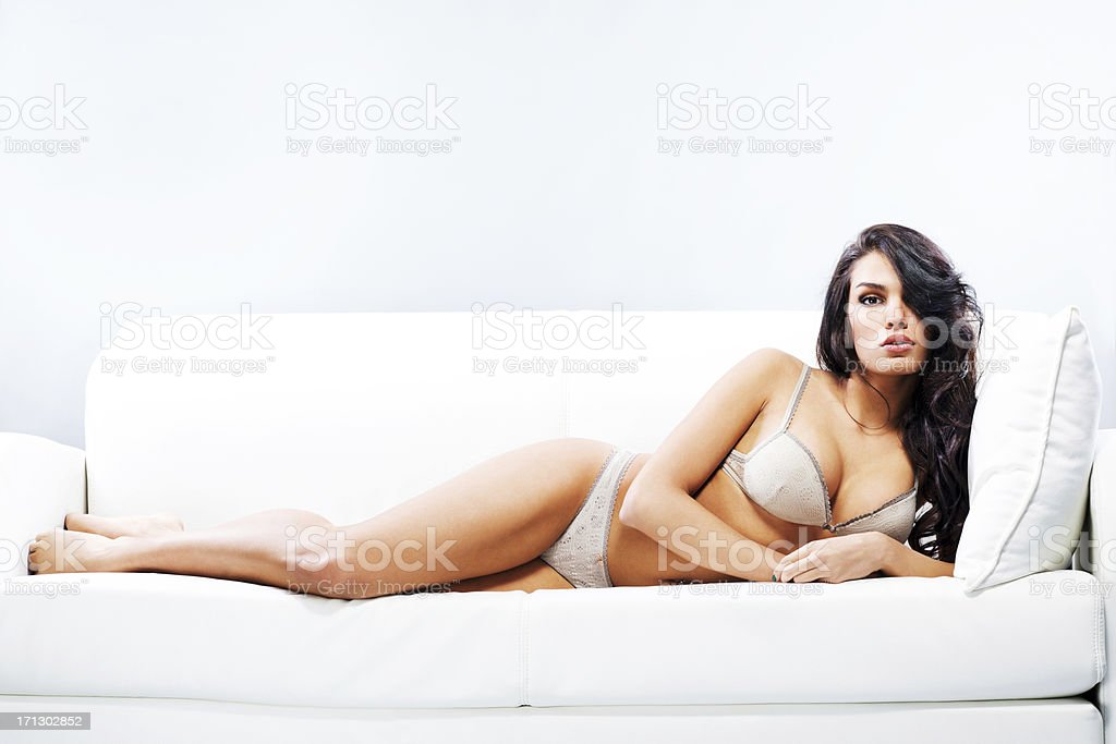 Attractive woman in underwear lying on sofa. stock photo