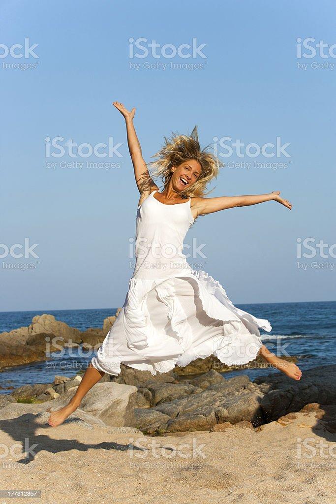Belle femme en blanc sauter en plein air. photo libre de droits