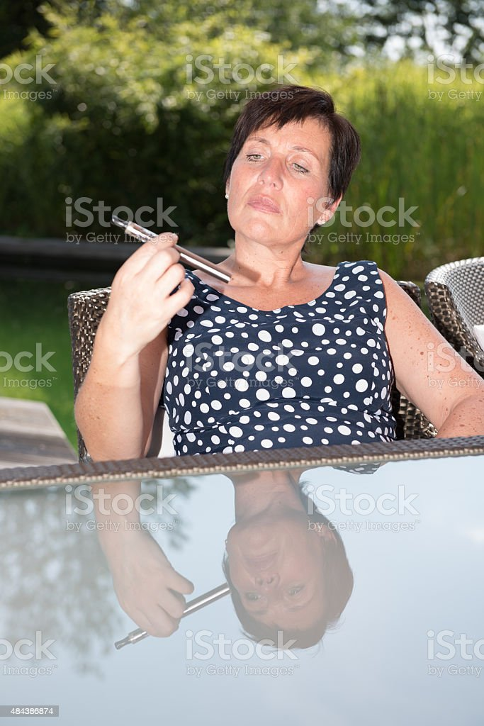 attractive woman is looking sceptical on  e-cigarette in garden stock photo