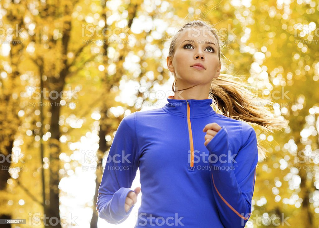 Attractive woman jogging outdoors in autumn stock photo