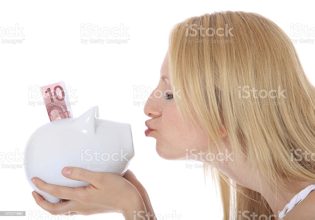 Attractive woman kissing piggy bank stock photo