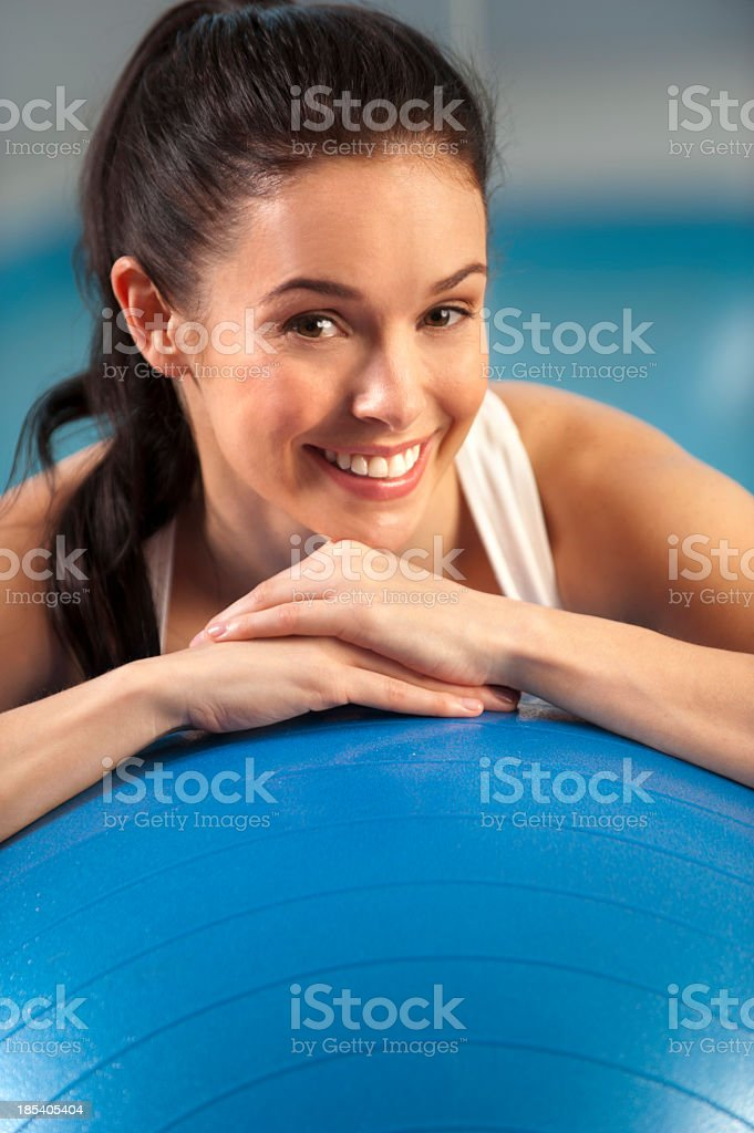Attractive woman leaning on an exercise ball royalty-free stock photo