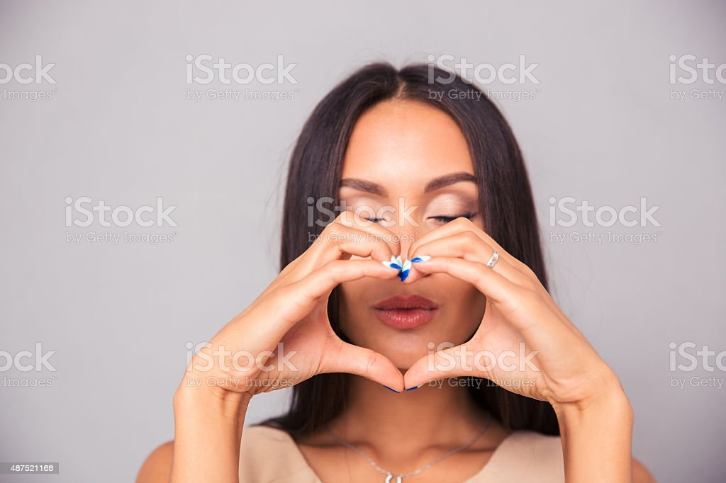 Attractive woman making heart with fingers stock photo