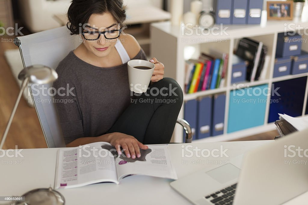 Attractive woman reading magazine at home stock photo