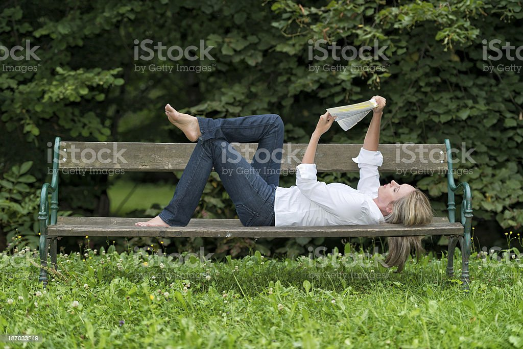 attractive woman reading on park bench royalty-free stock photo