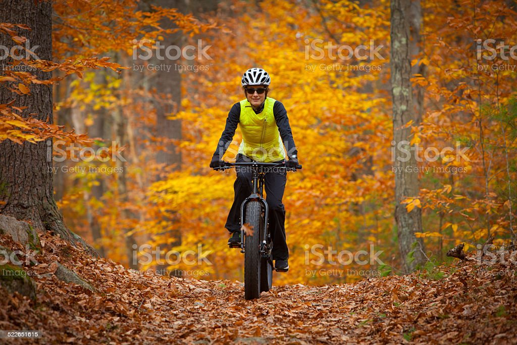 Attractive woman riding a fatbike in the fall stock photo