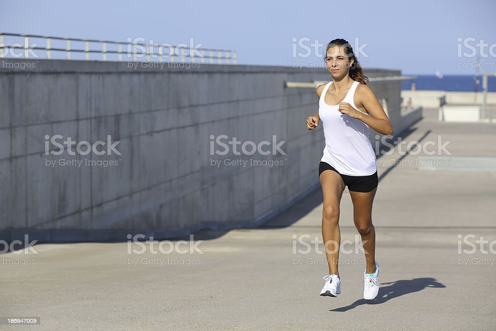 Attractive woman running on the asphalt royalty-free stock photo