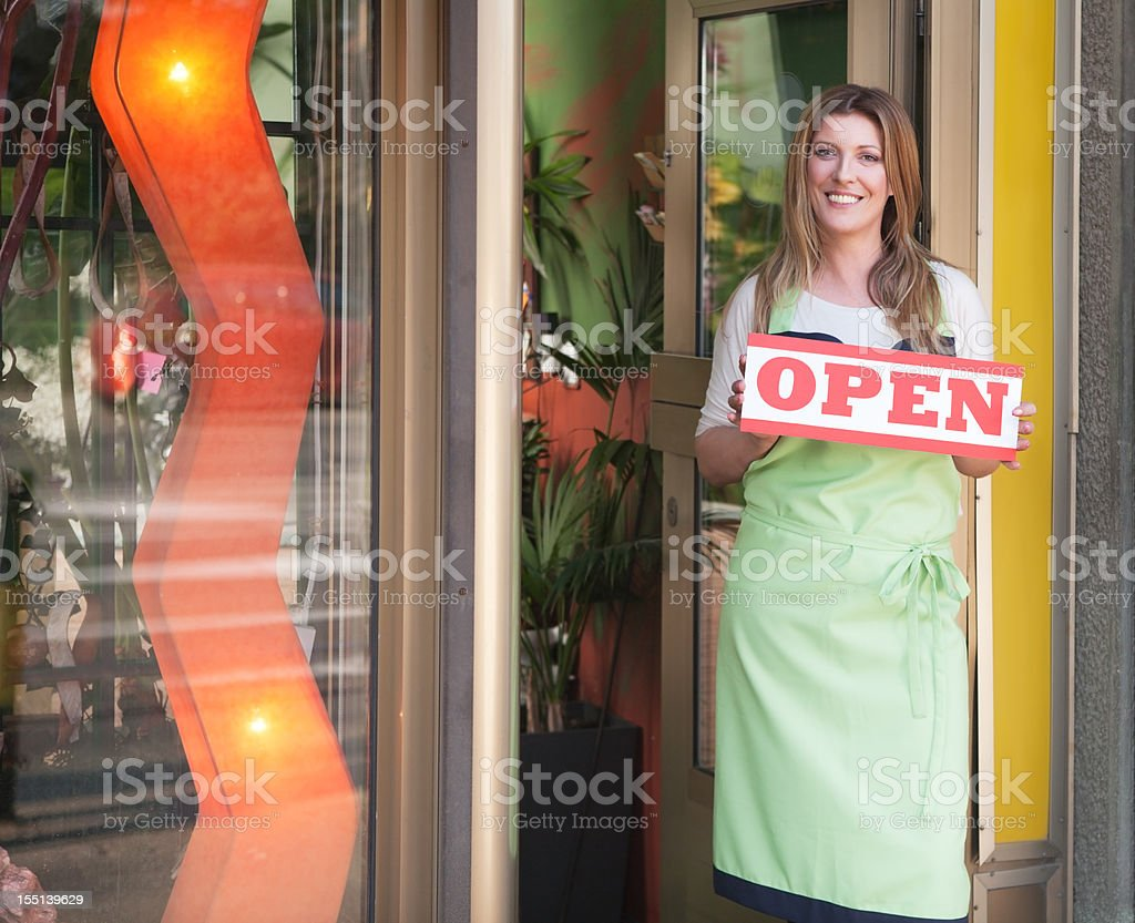 Attractive woman shop owner holding sing open. royalty-free stock photo