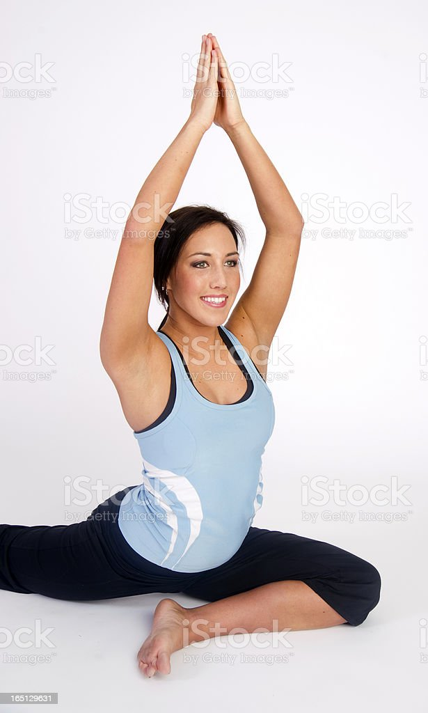 Attractive Woman Sits on Floor Practicing a Yoga Stretch Pose royalty-free stock photo