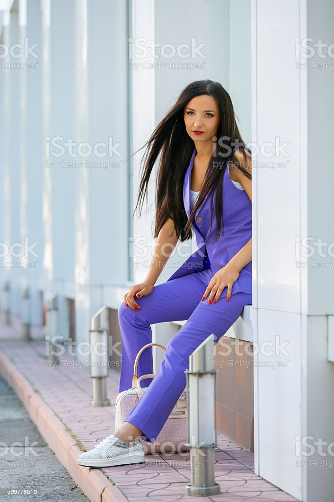 Attractive woman sitting at wall niche stock photo