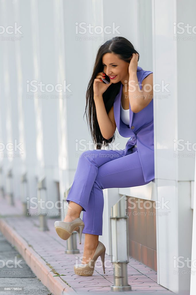 Attractive woman sitting at wall niche talking on phone stock photo