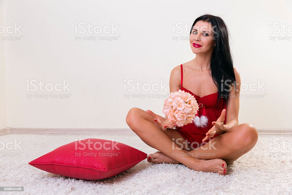 Attractive woman sitting cross legged with flowers in her hands stock photo