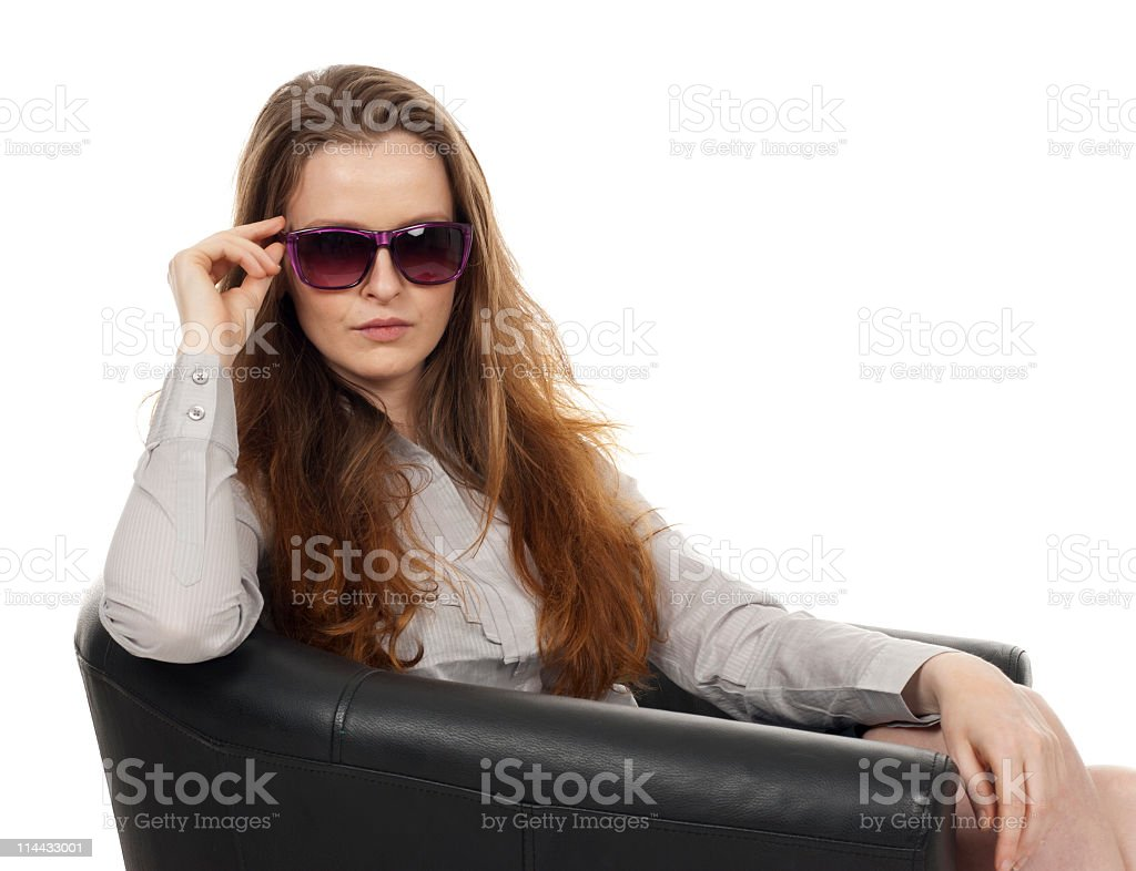 Attractive woman sitting in chair with sunglasses stock photo