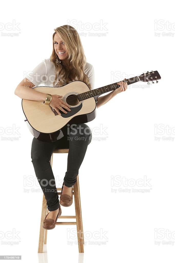 Attractive woman sitting on stool and playing a guitar stock photo