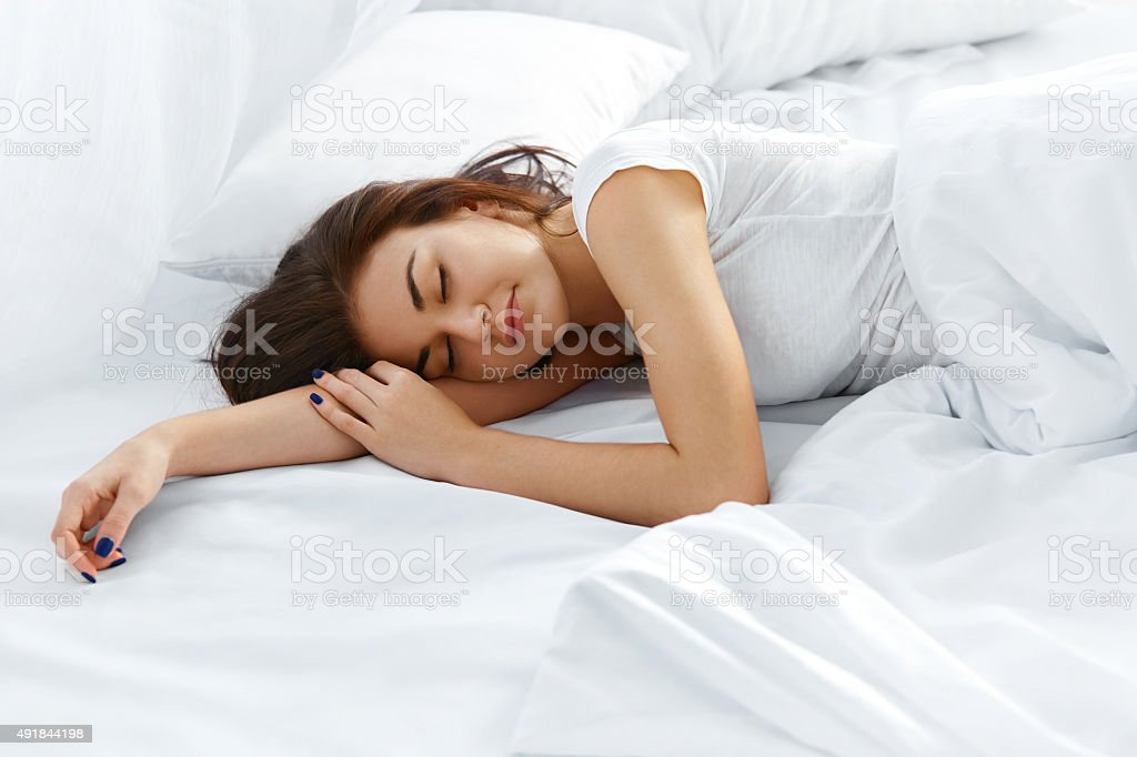 Attractive woman sleeping in bedroom stock photo
