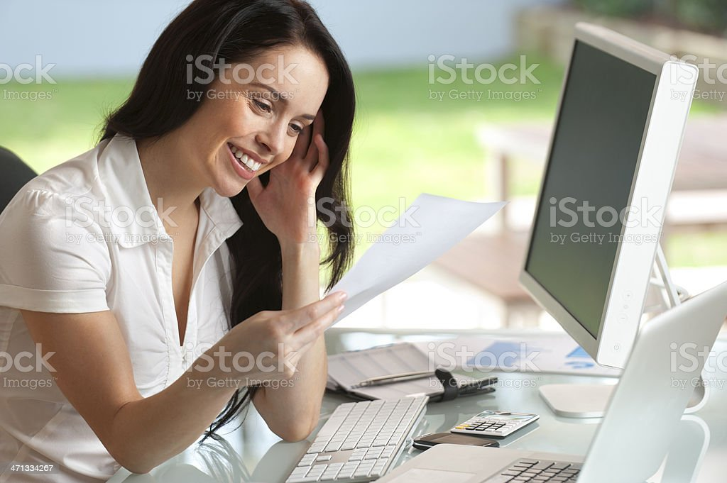 Attractive woman smiling reading a document royalty-free stock photo
