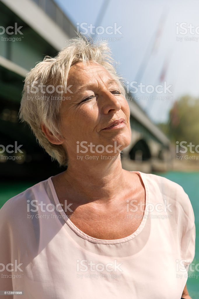 attractive woman standing on a the water and is relaxing stock photo