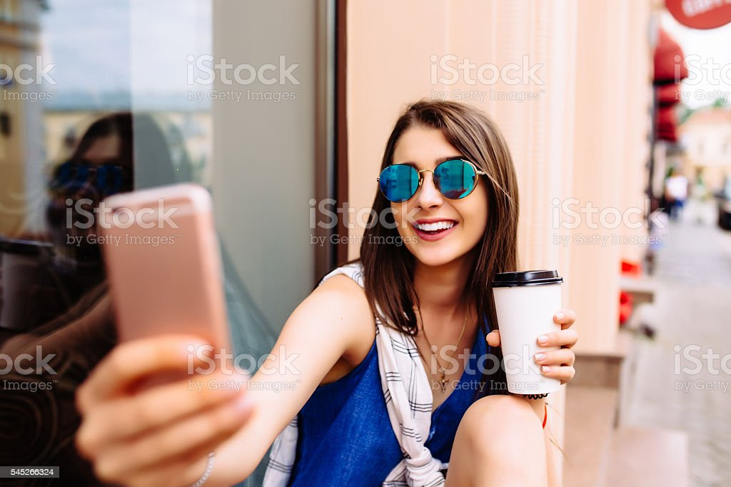 Attractive woman taking photo with take-out coffee on her phone stock photo