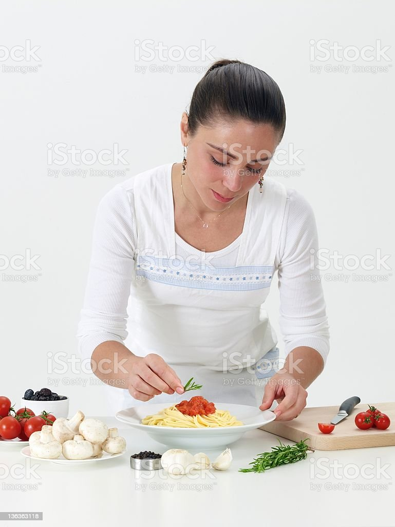 Attractive woman tasting freshly cooked spaghetti. Studio, white background. royalty-free stock photo